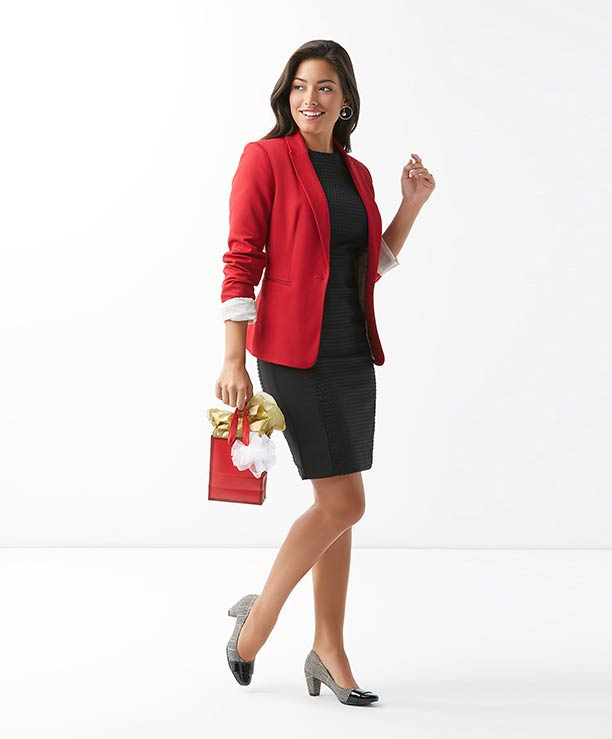 Woman carrying a gift bag and wearing a red jacket and heels