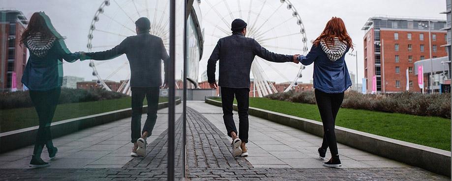 Two people walking towards a ferris wheel